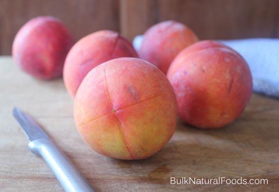 "Cut an ""X"" on the end of each peach."