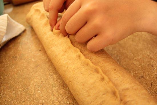 pinching the giant roll of dough